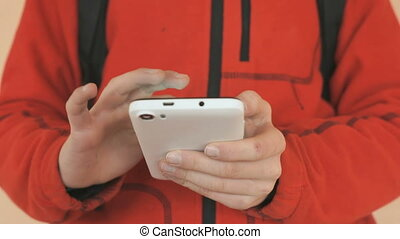 The schoolboy holding a white cellphone indoors. Close up