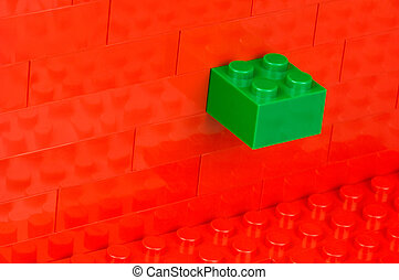 Green building block in a wall out of red building blocks