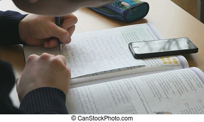 Student writes the text on a white sheet of paper - Student...