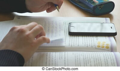 Schoolboy writes the text on a sheet on the lesson -...
