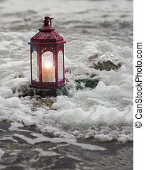 Candle lit lantern in water.
