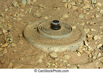 IED Landmine - An IED mine exposed in the desert sand