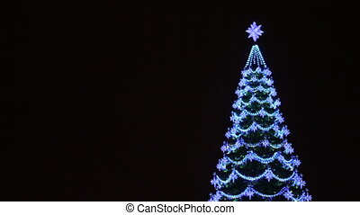 Christmas tree decorated with garlands and lanterns. With a place for text on a background.