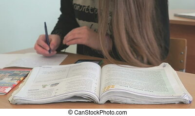 Pupil writes the text on white sheet of paper - Pupil...