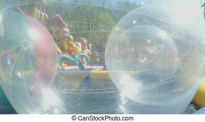 Big inflatable balls floating on the water in pool - The big...