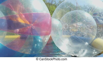 Big inflatable balls in opened pool. Sunny weather - Big...