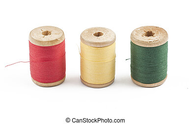 Three wooden multicolored thread coils on white background...