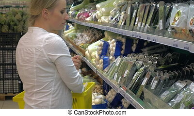 woman in a supermarket at the vegetable shelf shopping