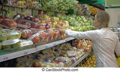 woman in a supermarket at the vegetable shelf shopping for...