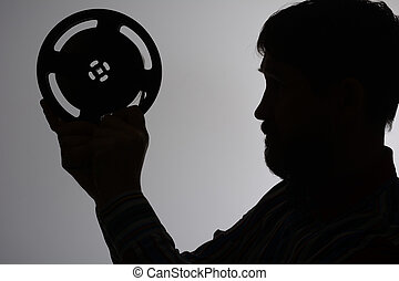 Silhouette of a bearded man looks at 16mm motion picture...