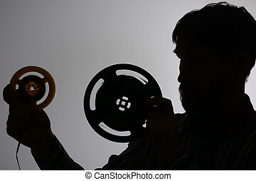 Silhouette of a bearded man looking at 2 of film reel.