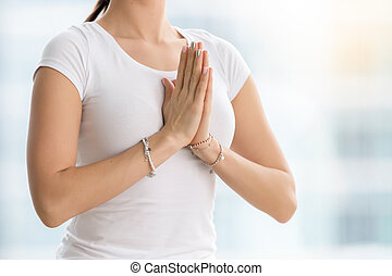 Woman in white t-shirt making namaste gesture, closeup -...