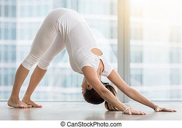Young woman in Downward facing dog pose against floor window...