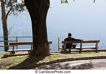 Lonely man sitting on bench with beautiful view of the mountains.