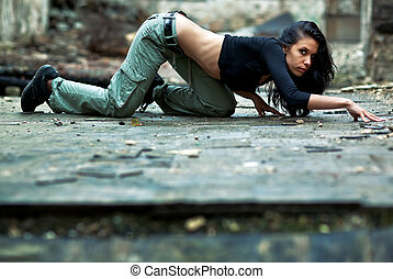 Young woman in a ruined building. Secretly crawling on a...