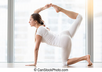 Young attractive woman in Bird dog pose against floor window...