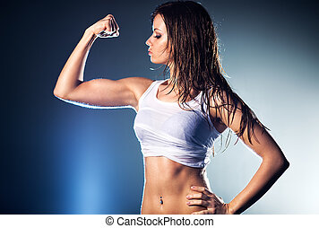 Young strong sexy woman showing her muscles.