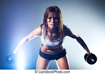 Young strong sexy woman with dumbbells Focus on face
