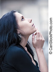 Young pensive woman looking up portrait