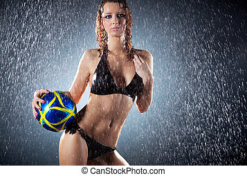 Young sexy woman football player. Water studio photo.