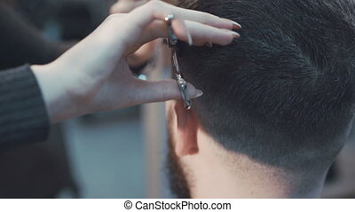 Female haircutter cutting the male hair in the barbershop...