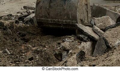 digger destroying asphalt and digging
