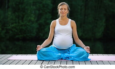 Young woman in the lotus position is practicing yoga in the forest next to the river. sitting on mats the wooden pier.