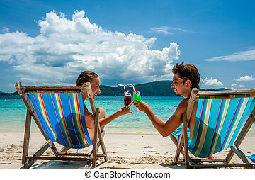 Couple in loungers on a beach at Thailand - Couple in...