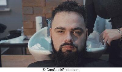 Young hipster man had his hair washed at a hair salon. -...