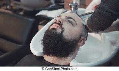 Young hipster man having his hair washed at a hair salon. 4K...