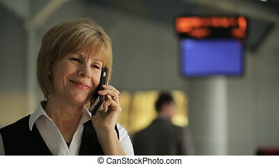 Close up shooting of woman talking on phone in departure...