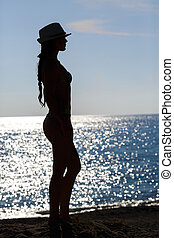 Silhouette of woman  on sea coast