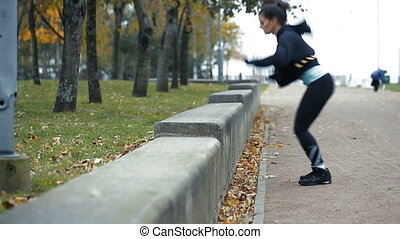 Woman outdoor at park doing fitness exercise jumps. - Woman...