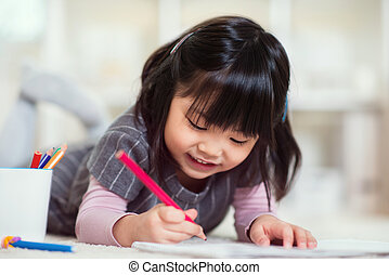 Pretty happy little japanese girl drawing with pencils at...