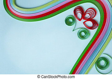 colorful paper quilling closeup on blue cardboard