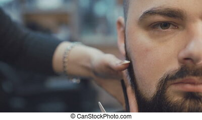 Female barber cuts the beard hair of the male client