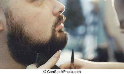 Female barber cuts the beard hair of the male client 4K.