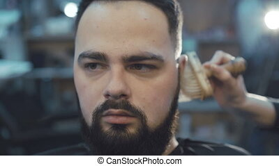 Female barber scratching the male beard hair with brush
