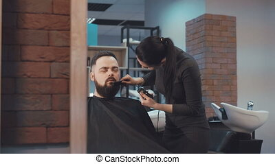 Look of female barber cuts the beard hair of the male client...