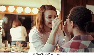 Makeup artist doing make up for young beautiful African...