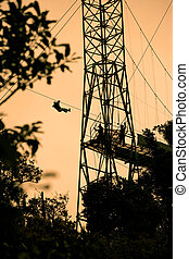 Tourists on zip line in Costa Rica - Silhoutte of tourists...