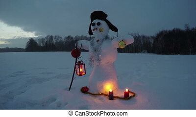 Snowman on new year evening field and candle lights, time lapse 4K