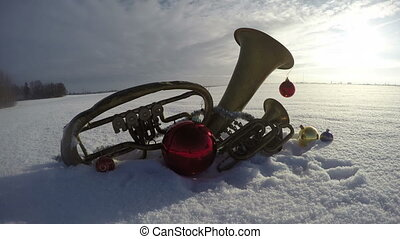brass musical instruments on snow with Christmas...
