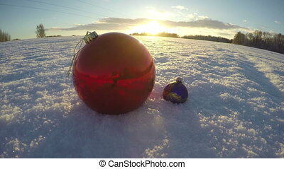 Christmas bauble on snowy december field and sunset light, time lapse