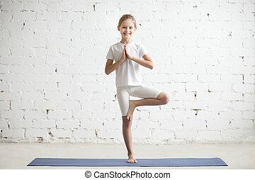 Girl child in Vrksasana pose, white studio background -...
