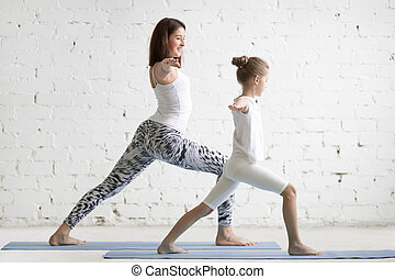 Kids yoga teacher training with a little girl Virabhadrasana...