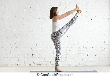 Young woman in Extended Hand to Big Toe pose, profile -...