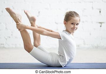 Smiling girl child in dhanurasana pose, white studio...