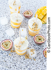 Homemade frozen popsicles with fresh mango and passion fruit