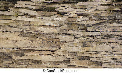 Weathered limestone cliff background with wavy strata - A...